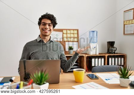 Young hispanic man wearing business style sitting on desk at office smiling cheerful presenting and pointing with palm of hand looking at the camera.