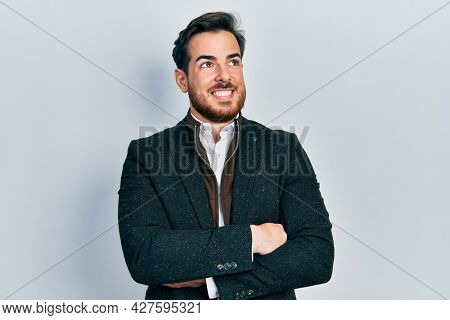 Handsome caucasian man with beard with arms crossed gesture smiling looking to the side and staring away thinking.