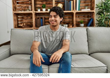 Young hispanic man wearing casual clothes sitting on the sofa at home looking away to side with smile on face, natural expression. laughing confident.