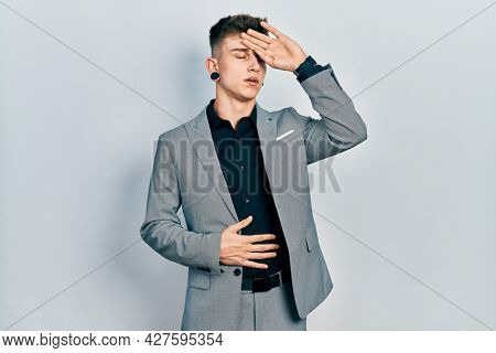 Young caucasian boy with ears dilation wearing business jacket touching forehead for illness and fever, flu and cold, virus sick