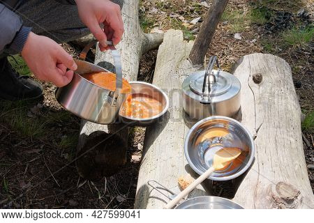 Tourist Food In Outdoor Activities. Soup In Bowls On Wooden Logs In The Forest. Camping Food Making.
