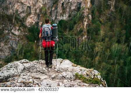 A Traveler With A Backpack In The Mountains, Rear View. The Concept Of A Sporty Lifestyle In Travel.