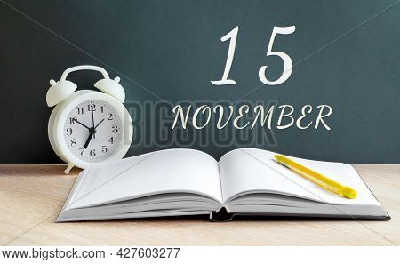 November 15. 15-th Day Of The Month, Calendar Date.a White Alarm Clock, An Open Notebook With Blank