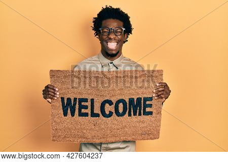 Young african american man holding welcome doormat sticking tongue out happy with funny expression.