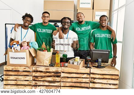 Group of young african american volunteers smiling happy and hugging holding donations banner at charity center.