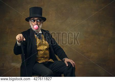Cute Senior Smiling Man, Gentleman, Aristocrat Or Actor Watching Movie Isolated On Dark Vintage Back
