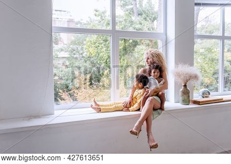 Young Blond Caucasian Woman Hugging African American Children, Daughter And Son. Happy Family Is Sit