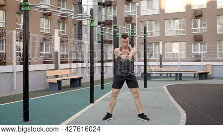 A Young Man Lunges With Kettlebells. A Man Lifts A Kettlebell While Standing In The Yard. Bodybuilde