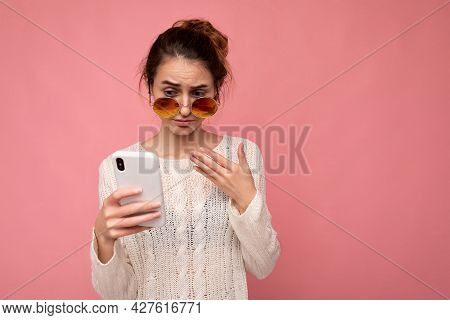Photo Of Attractive Dissatisfied Young Woman Wearing Casual White Blouse And Colorful Sunglasses Iso