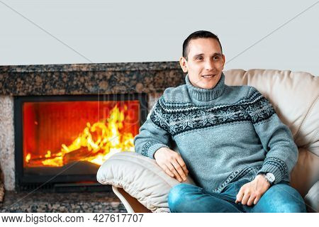 A Young Man In A Knitted Sweater Sits In A Leather Chair Against The Background Of A Fireplace With