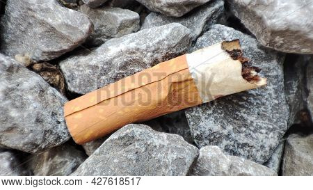 Discarded Cigarette Butt On Gravel. The Cigarette Butt On The Ground. Environment Protection. Pollut