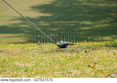 Blurred Golf Club And Golf Ball Close Up In Grass Field With Sunset. Golf Ball Close Up In Golf Cour