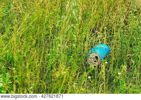 Blue Beer Can In Green Grass. A Used, Open, Disposable Metal Beer Can, Thrown To The Ground Like Rub