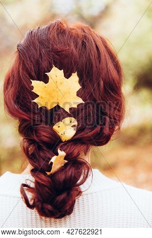Autumn Woman. Young Woman With Yellow Autumn Leaves In Red Hair. Beautiful Girl Walking Outdoors In