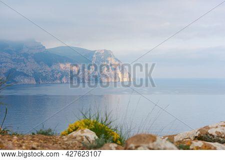 Mountains Sea Flowers In Spring. Cape Ai-ya Balaklava In A Light Blue Haze. A Silent Beautiful Sea A