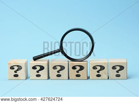 Wooden Cubes With Question Marks And A Magnifying Glass On A Blue Background. The Concept Of Finding