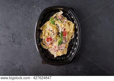 Tagliatelle Carbonara In Black Plastic Container On Dark Graphite Background Top View. Designer Food