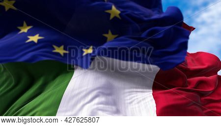 The National Flag Of Italy Waving In The Wind Together With The European Union Flag Blurred In The F