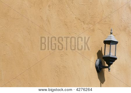 Old Lamp On The Brown Wall With Shadow.