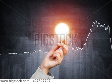 Human Hand With Glowing Incandescent Lamp On Grunge Background With Business Infographics. Organizat