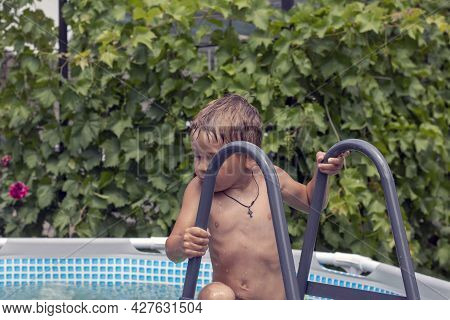 Children In The Pool Near The House Swim And Indulge. Two Brothers Are Swimming In A Frame Pool. Blu