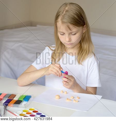 A Girl Sculpts From Clay In A White Sunny Room. Home Art Teaching Concept. Creative Child At Work. C