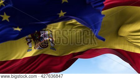 The National Flag Of Spain Waving In The Wind Together With The European Union Flag Blurred In The F