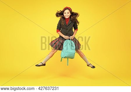Happy Small Kid In Formal Uniform Hold School Bag Jumping In Midair Yellow Background, Schooling