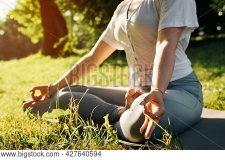 Close-up Of Young Yoga Woman Practicing Morning Meditation, Sitting In Lotus Position On Sports Mat,