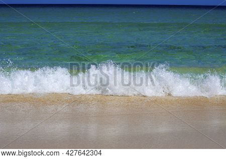 Crystal Clear Blue Sea Water In Various Shades, White Foam And  Wave Flooding The Sandy Beach. Fuert