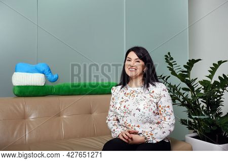 Mid Cheerful Adult Woman Sitting On Sofa In Corridor Of Dentist Reception Smiling Against Big Toothb