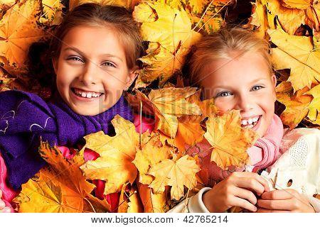 Porträt von zwei süße Mädchen-Schwestern, die auf die Blätter im Herbst Park liegen.