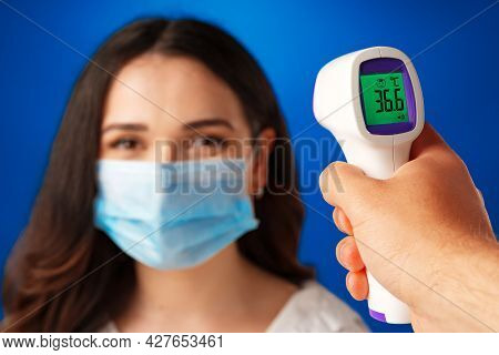 Brunette Woman Getting Temperature Screening With Infrared Thermometer Against Blue Background