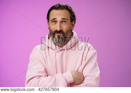 Unsure Troubled Caucasian Bearded Adult Guy With Earring Pink Hoodie Press Lips Frowning Counting Mi