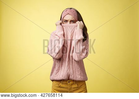 Sad Silly, Gloomy Cute Young Girl Hiding Face In Sweater Collar Pulling Clothes On Nose Frowning Dis