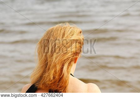 Young Woman In Bikini On The Beach With Her Hand Dissolves Her Hair. A Tanned Woman On Vacation Is R