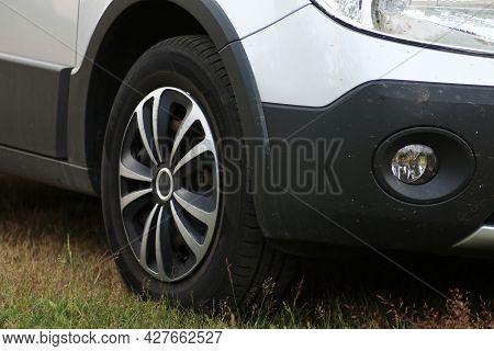 Front Wheel Of A Passenger Car Close-up. Automotive Wheel Caps. Car Tuning.