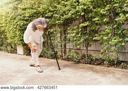 Senior Asian Woman Aching Knee With Osteoarthritis During Walking: Knee Injury Inflammation Is More