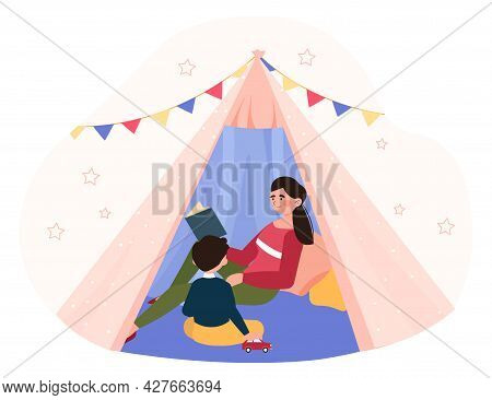 Taking Care Of Children Concept. Mother Reading Book And Telling Story With Son In The Teepee Tent.