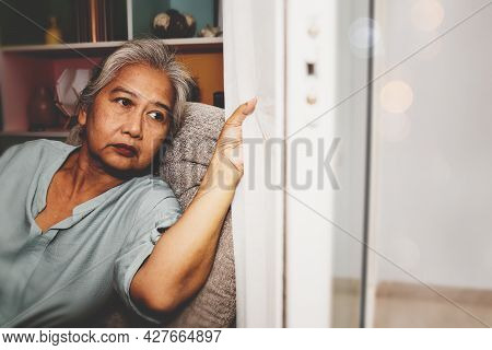 Elderly Asian Woman Sits At Home To Keep Her Health Safe From The Coronavirus. (covid-19) She Looked