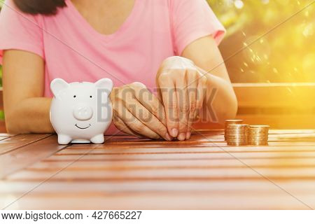 Money Saving Concept : Asian Woman Hands Counting Stacked Coins To Put A Piggy Bank For The Future.