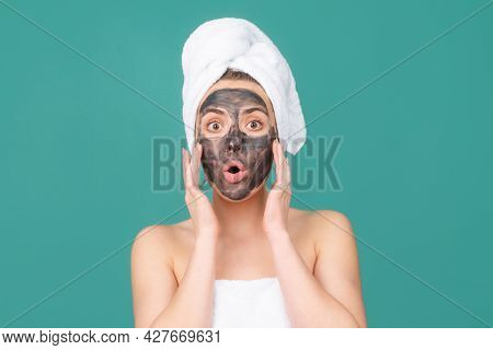 Surprised Woman With Mud Facial Mask, Face Clay Mask Spa. Beautiful Woman With Cosmetic Mud Facial P