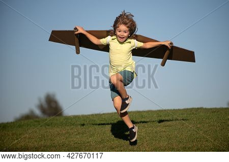 Child To Be Pilot. Kid With Paper Wings Flying. Summer Vacation And Travel Concept. Funny Child Boy