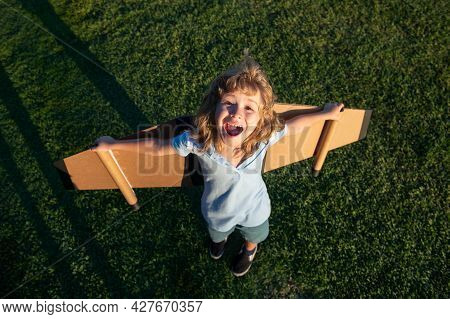 Excited Kid With Backpack Wings. Child Playing Pilot Aviator And Dreams Outdoors In Park. Smiling Ki