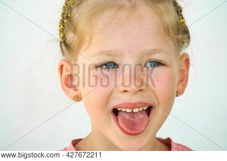Cheerful Child. Girl Laughs Close-up Of The Face On A White Background. A Little Girl Show Tongue Th
