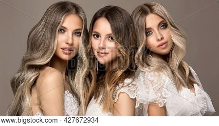 Three Beautiful Girls In  White Wedding Dresses  With Hair Coloring In Ultra Blond. Stylish Hairstyl