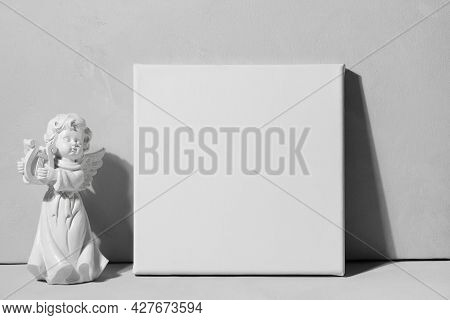 Blank Canvas And Angel Figurine Against Grey Wall. Mockup Poster. White Canvas, Gallery Wrap. Valent