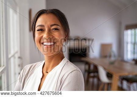 Portrait of a beautiful african woman smiling while looking at camera. Mature black woman in casual standing near window at home. Close up face of laughing cheerful lady near window with copy space.