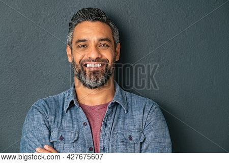 Close up face of handsome mature man with beard looking at camera. Happy mid adult indian man isolated against grey wall. Portrait of smiling mixed race guy on gray background with copy space.