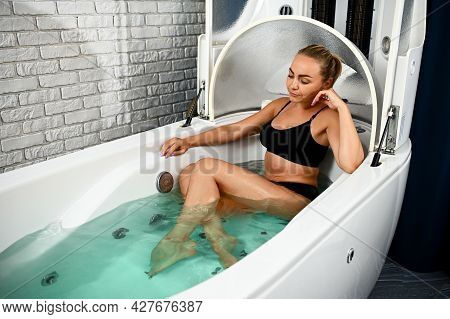 Pretty Woman In Black Swimsuit Receiving Vibro Massage While Relaxing In The Bathtub In A Spa Capsul